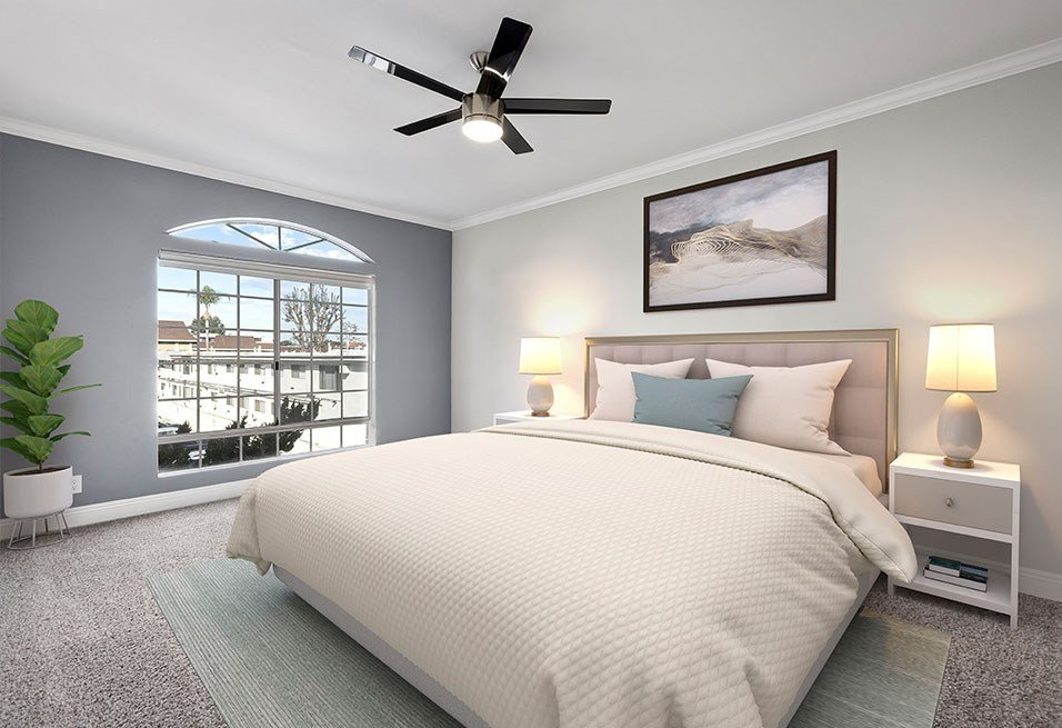 Carpeted bedroom featuring beautiful natural lighting and ceiling fan.