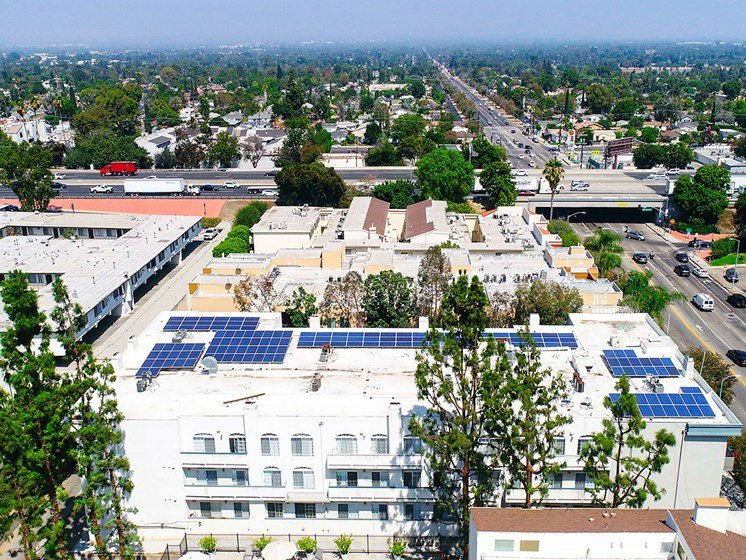 Aerial drone view of Chateau Encino showing energy-efficient white roof, solar panels, and access to 101 freeway.