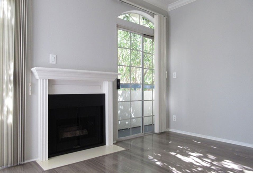 Fireplace with overhanging mantle and large windows with patio access.