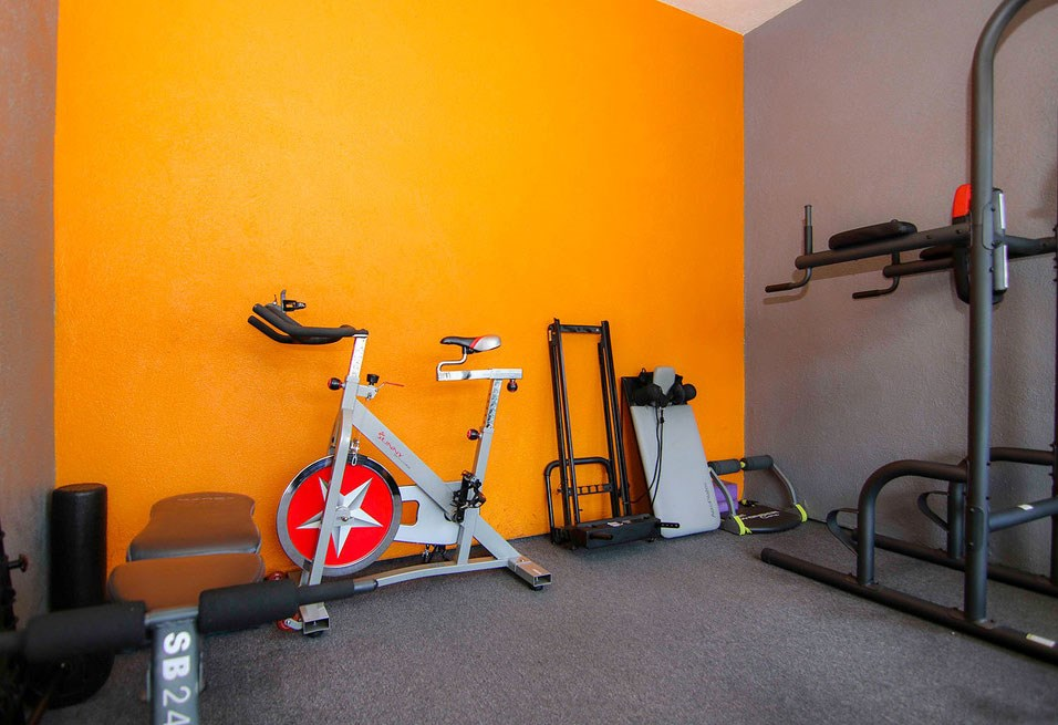 On-site gym with stationary bike and weight equipment.