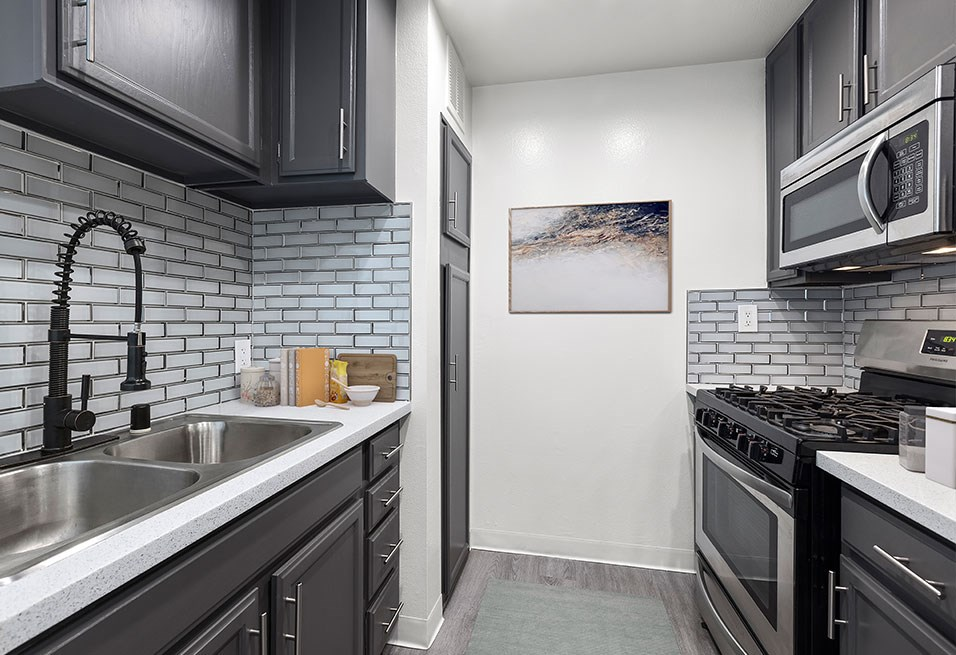 White tiled kitchen with stainless steel fridge, oven, microwave, and fixtures.