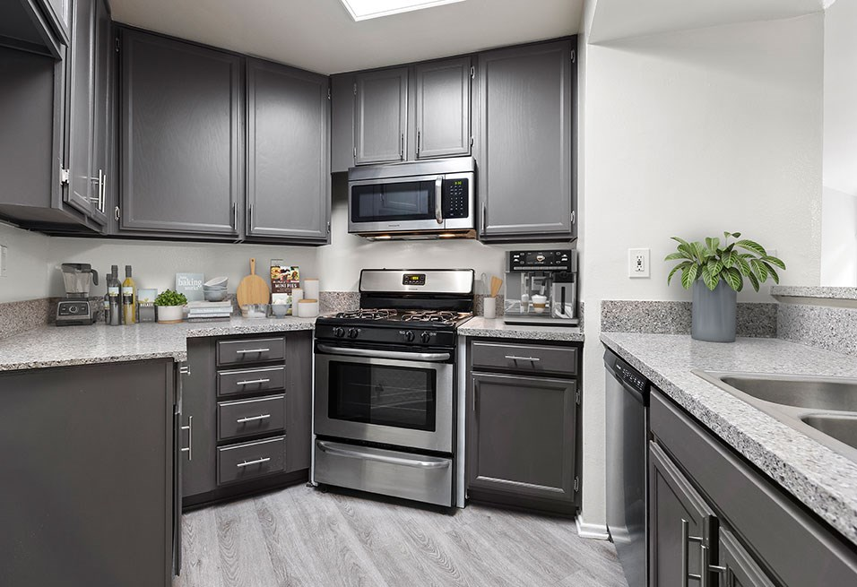 Stone tiled kitchen with stainless steel oven, microwave, and fixtures.