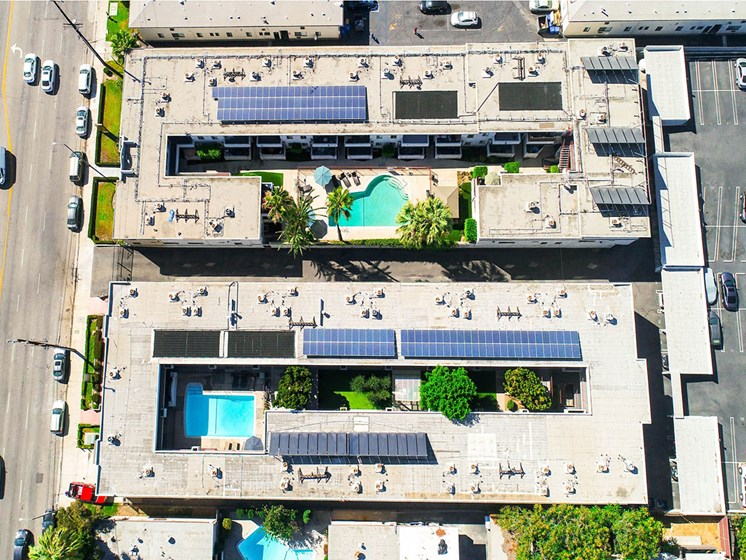 Aerial drone image of Sherman Oaks Gardens, showing solar panels and energy-efficient white roof.
