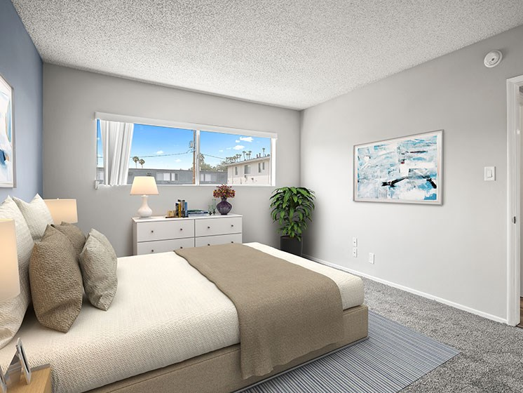 Carpeted bedroom with large window for natural light.