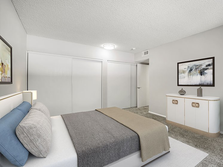 Large carpeted private bedroom showing sliding door closets.