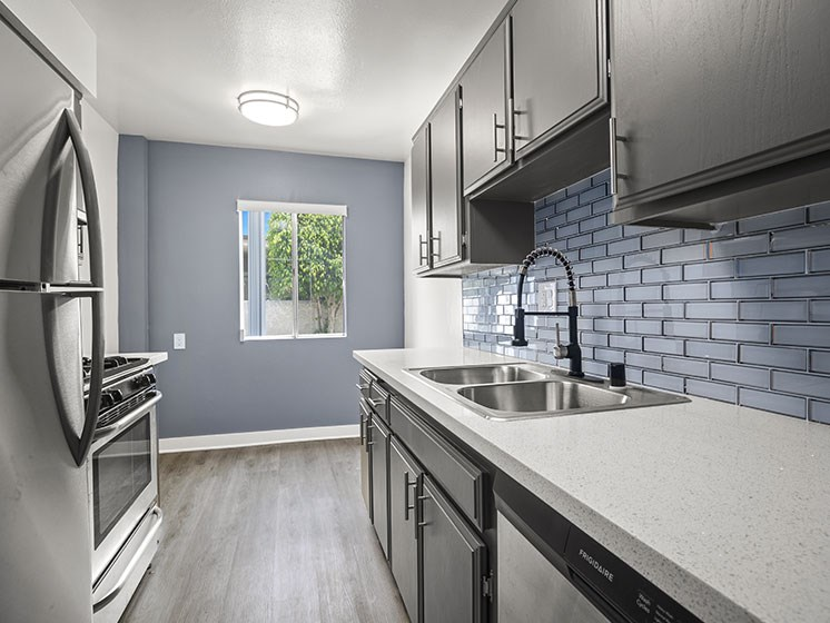 Tiled kitchen with stainless steel oven, microwave, and fridge.