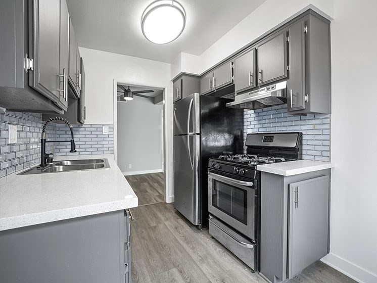Tiled kitchen with stainless steel oven, fridge, and fixtures.
