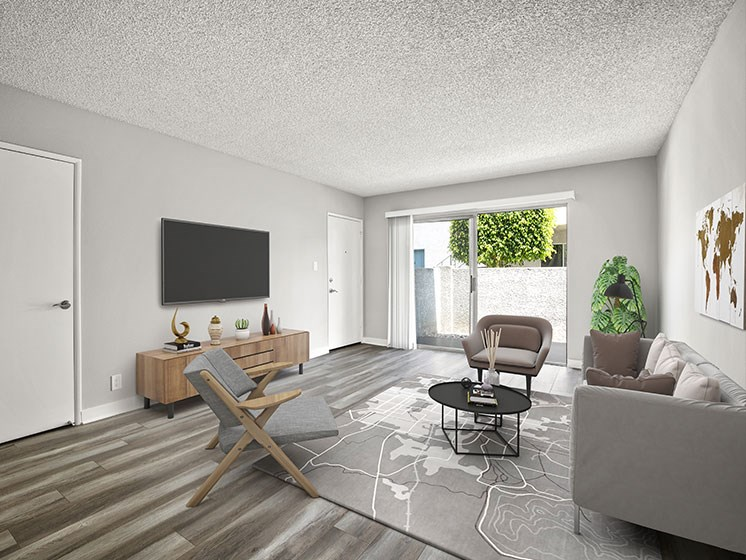 Hardwood floored living room with view of private balcony.