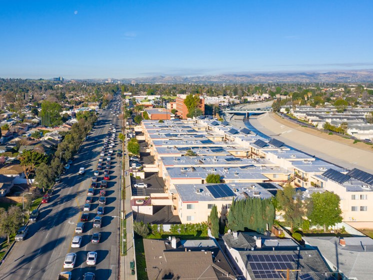 Aerial drone photo of Riverbridge Apartments showing solar panels and energy-efficient white roofs.