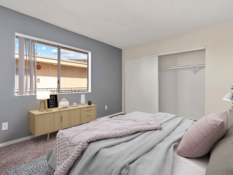 Carpeted bedroom with accent wall and large natural light window.