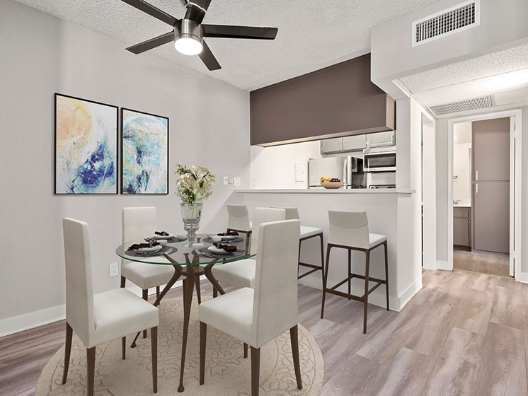 Dining room with view of ceiling fan and bar seating in kitchen.