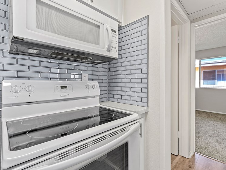 White tiled kitchen with stainless steel oven and microwave.