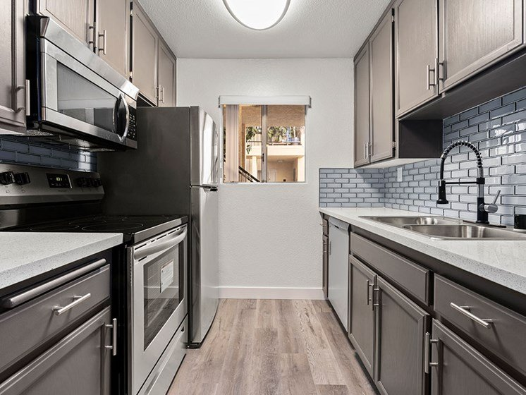 White tiled kitchen with stainless steel oven, microwave, and fridge..