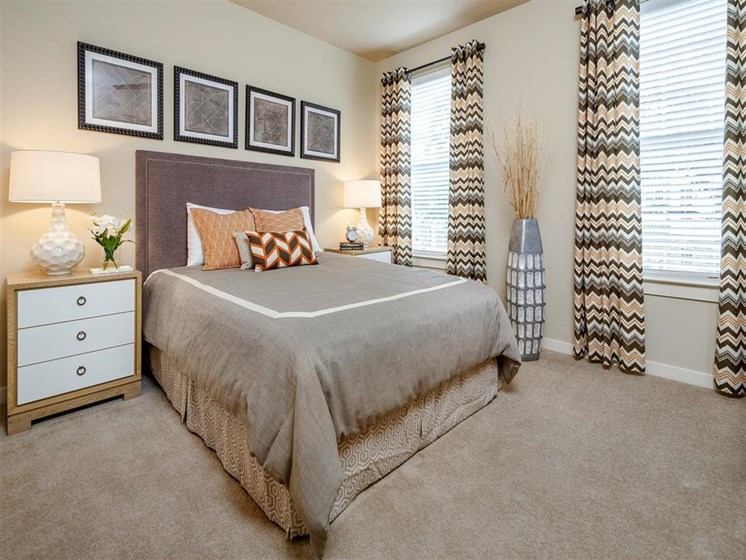 Bedroom with two windows and plush carpeting