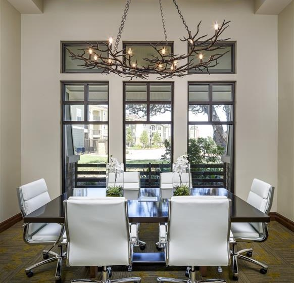Conference room with large windows and six seated conference table
