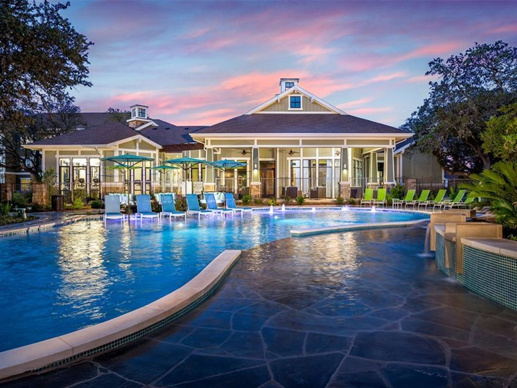 Sunset pool view with poolside seating outside resident clubhouse