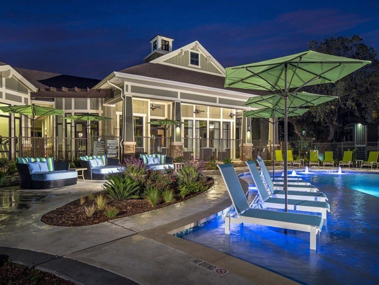 Nighttime pool view with in and poolside lounge seating