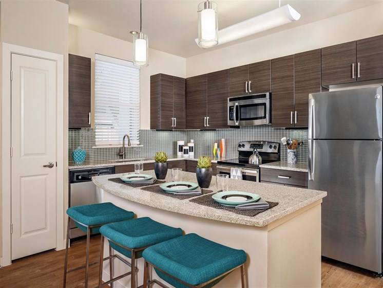 Kitchen with granite countertops, stainless steel appliances, wood-style floors, and modern lighting over island