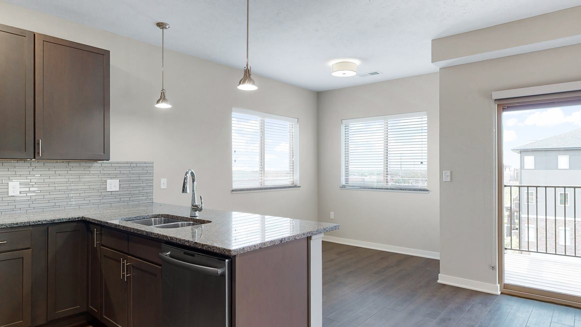 The 2 bedroom Marigold with den floor plan at WH Flats features an open eat-in kitchen area with granite countertops and large peninsula.