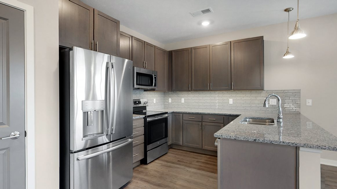 This 2 bedroom Marigold with den floor plan at WH Flats features a tile backsplash (available in some homes), stainless steel appliances, granite countertops and large peninsula.