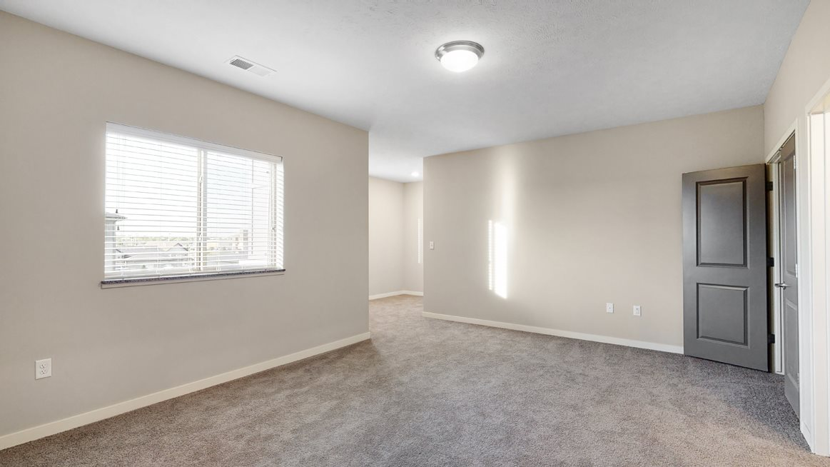 The large bedroom with den area in the Marigold with den floor plan is perfect for a desk or reading nook.