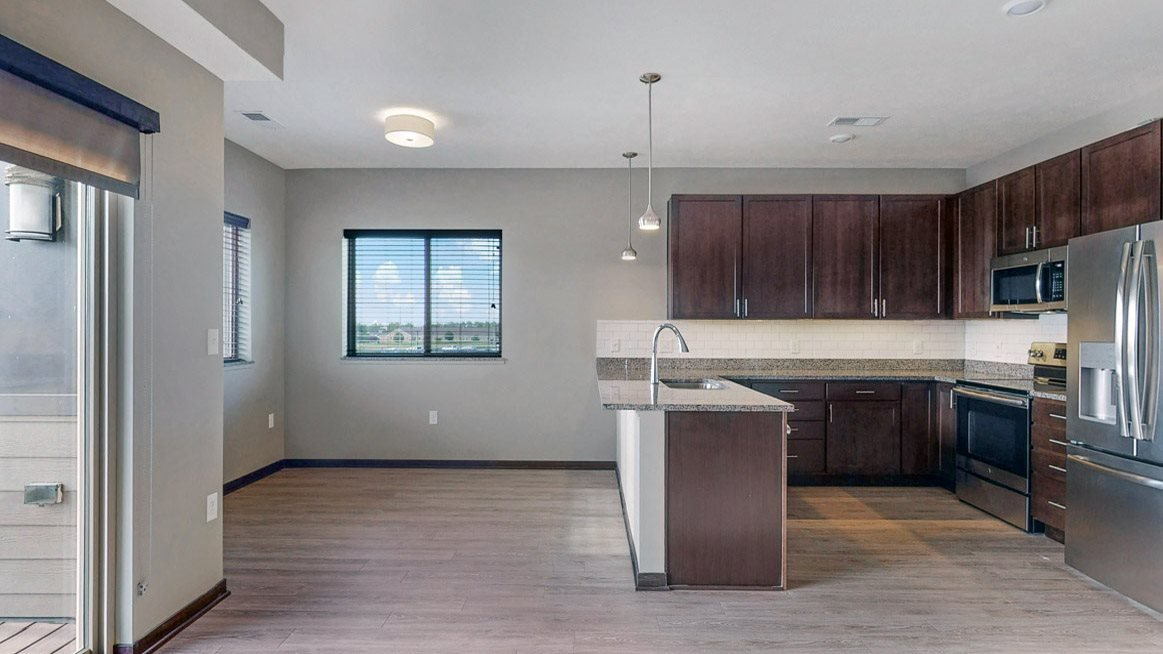 The 2 bedroom Snowdrop with den floor plan at WH Flats features an open eat-in kitchen area with granite countertops and large peninsula.