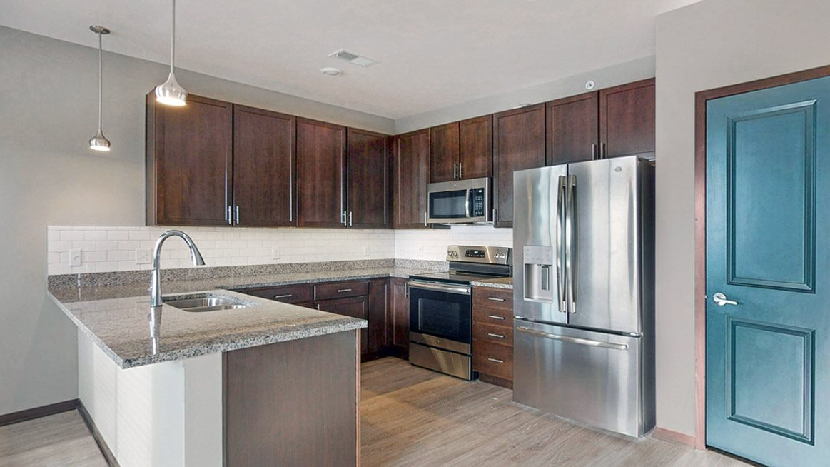 The 2 bedroom Snowdrop with den floor plan at WH Flats features an open kitchen with granite countertops and large peninsula.