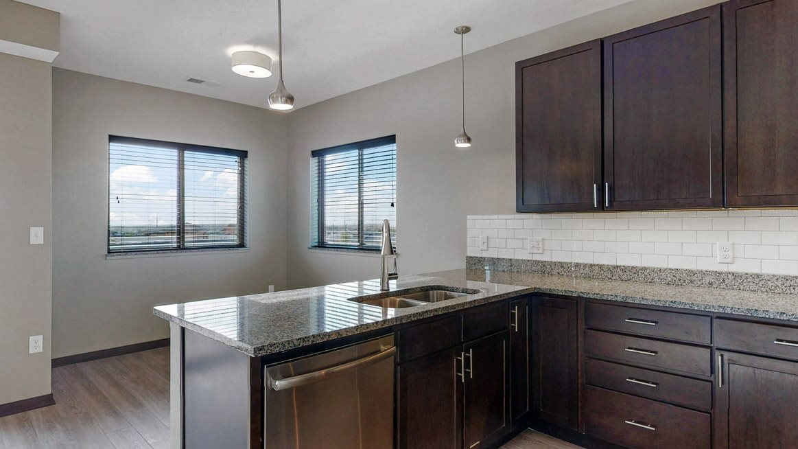 This 2 bedroom Snowdrop with den floor plan at WH Flats features a tile backsplash (available in some homes), stainless steel appliances, granite countertops and large peninsula.