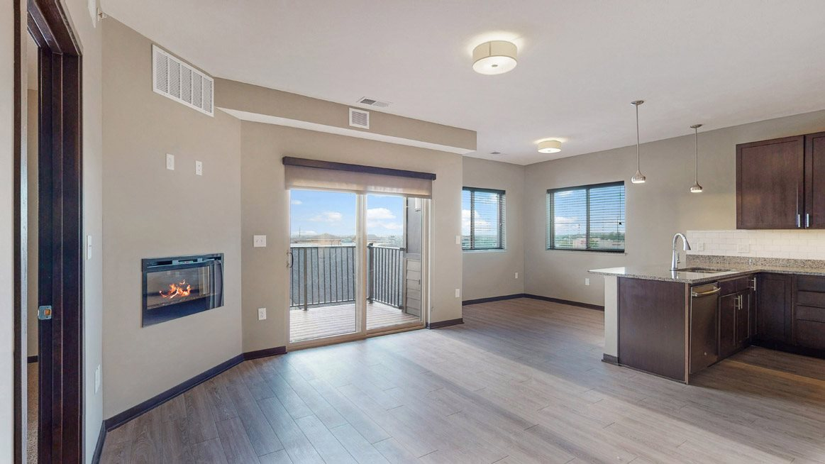 The 2 bedroom Snowdrop with den floor plan at WH Flats features natural light and a spacious dining and living area with electric fireplace.