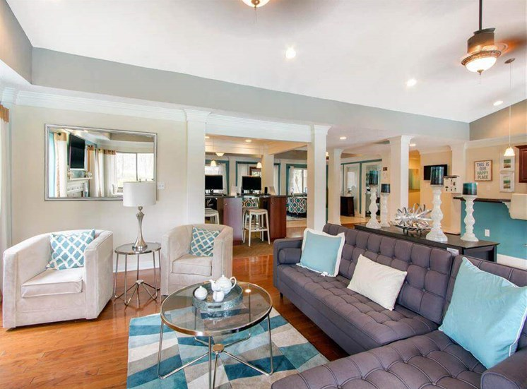 Clubhouse Seating Area with Grey Sectional Couch Coffee Table on Area Rug and White Armchairs