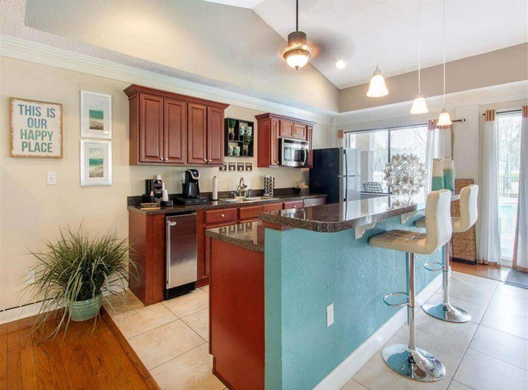 Clubhouse with Kitchen with Brown Cabinets and BReakfast Bar with Stools