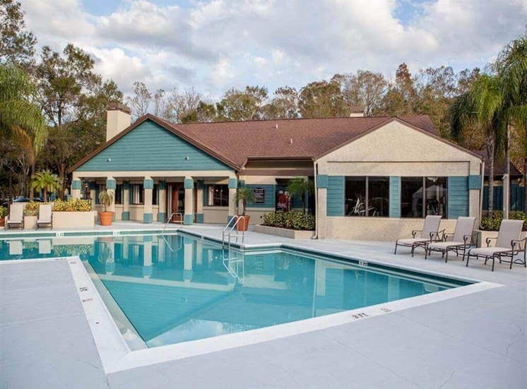 Leasing Office Exterior with Swimming Pool and Sun Deck with Lounge Chairs with Trees in the Background