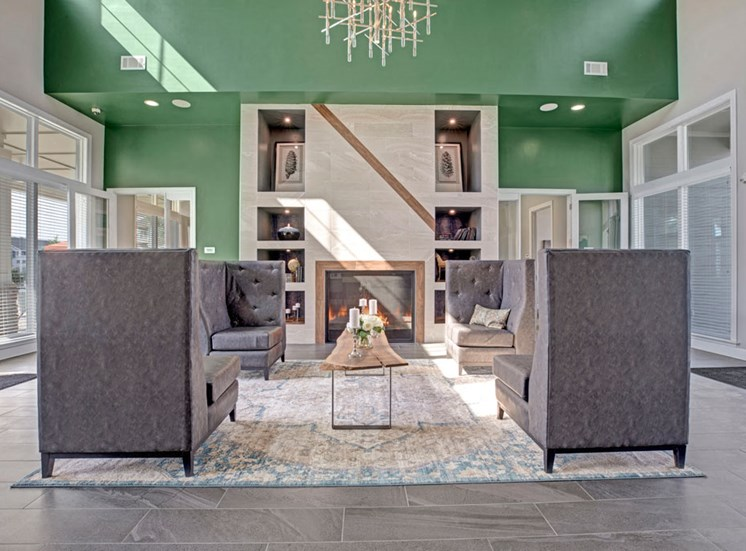 Lobby area that has couch like chairs, table in the center, fire place, dark concrete like floors, and big windows at Ascent at Mallard Creek Apartments in Charlotte, NC