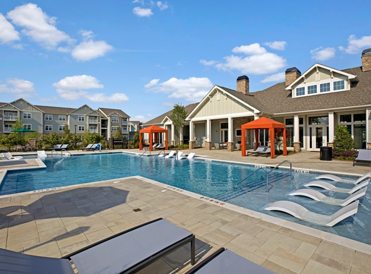 Swimming Pool. Big spacious pool with chairs in shallow end, loungers, cabanas at Ascent at Mallard Creek Charlotte, NC
