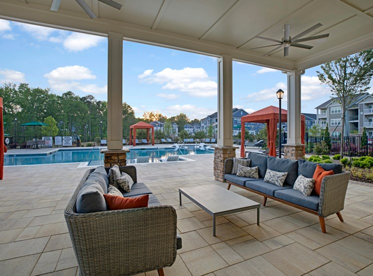 Pool view at Ascent at Mallard Creek Apartment Homes. Couches, table, cabanas, big pool, outside fans, and tile concrete flooring. At Ascent at Mallard CreekCharlotte, 28262