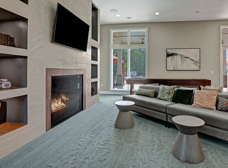 Living room at Ascent at Mallard Creek Apartment Homes. Carpet area with a fire place, tv, couch, pool table, tables, and big windows.