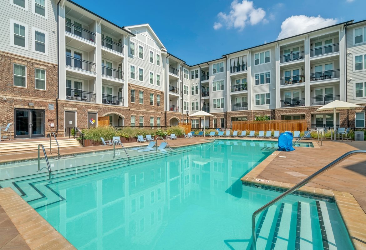 Apartments for Rent in Cornelius, NC - The Junction at Antiquity Swimming Pool Surrounded by Lounge Chairs, Shaded Tables, and Beautiful Landscape