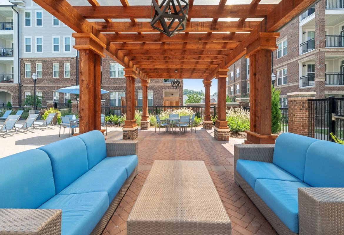 Cornelius Apartments for Rent - The Junction at Antiquity Pergola Covered Outdoor Lounge Next to Pool with Couch and Table Seating