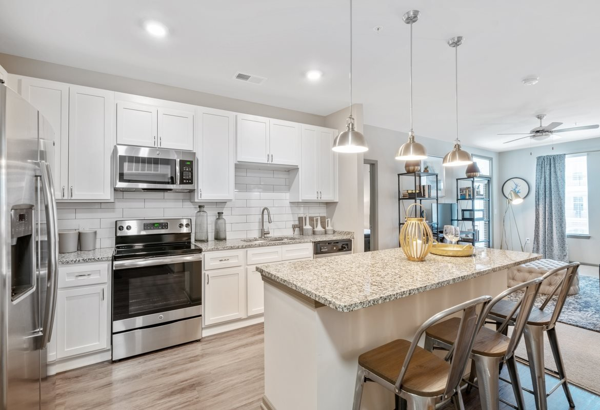 Luxury Apartments in Cornelius, NC - The Junction at Antiquity Apartments Kitchen with White Cabinetry and an Island with Bar Seating