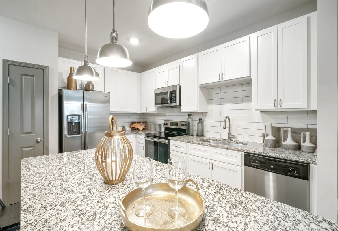 Dog Friendly Apartments in Cornelius, NC - The Junction at Antiquity Modern Kitchen with Stainless Steel Appliances, Quartz Counters, Large Island, and White Cabinetry