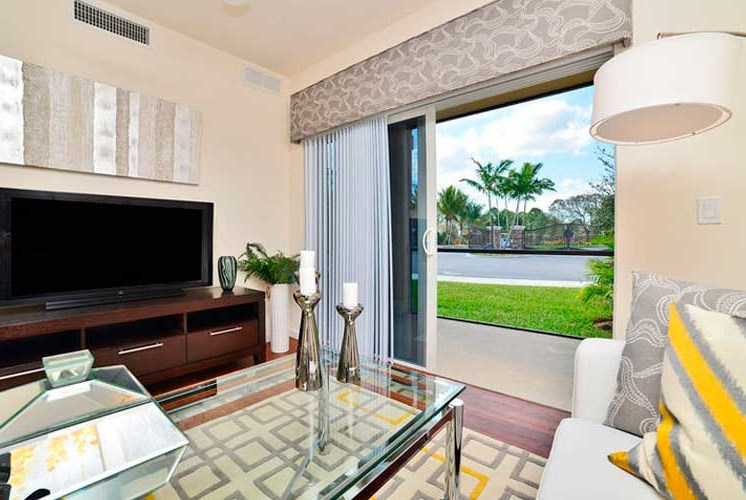 Gorgeous Modern Living Room with Bright Open Windows and Hardwood Flooring (in Select Units) at Casa Brera at Toscana Isle Apartments, Lake Worth, FL 33463