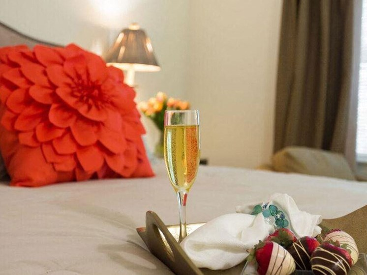 Glass of Champagne on the Bed at The Preserve Apartments in Walpole, MA