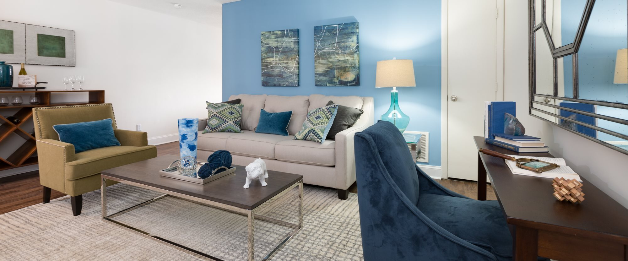 Living room interior with light blue accent wall, fully decorated with a rug, two accent chairs, a light gray sofa, and a wooden desk
