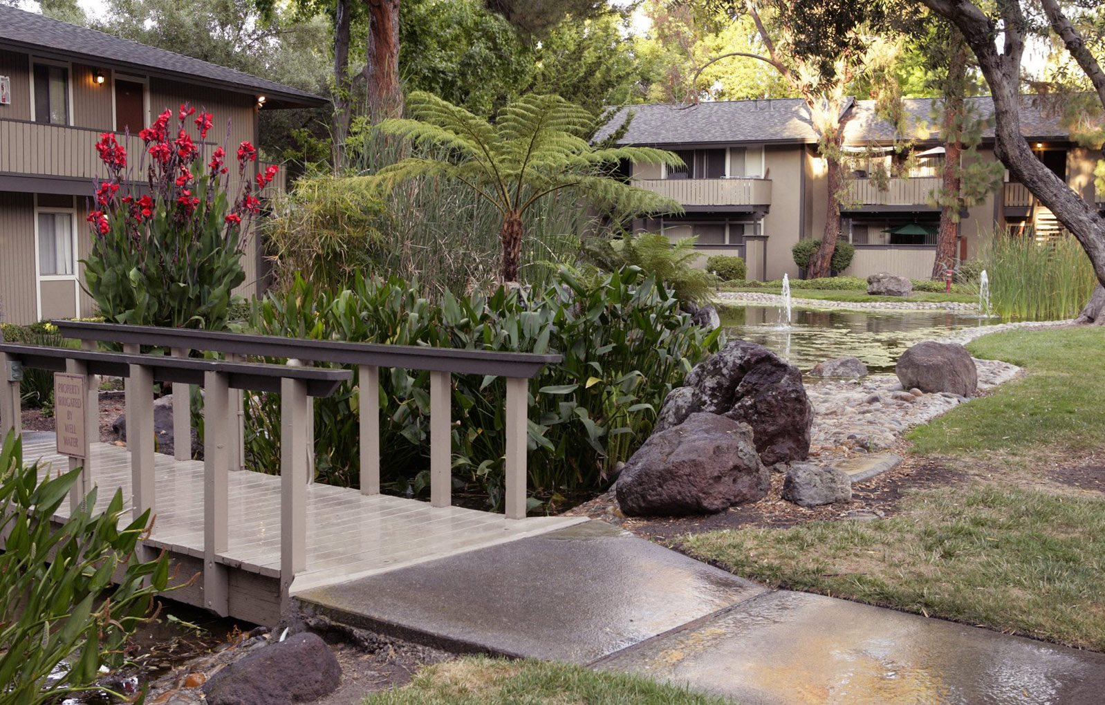 Lush landscaping with little bridge over community pond