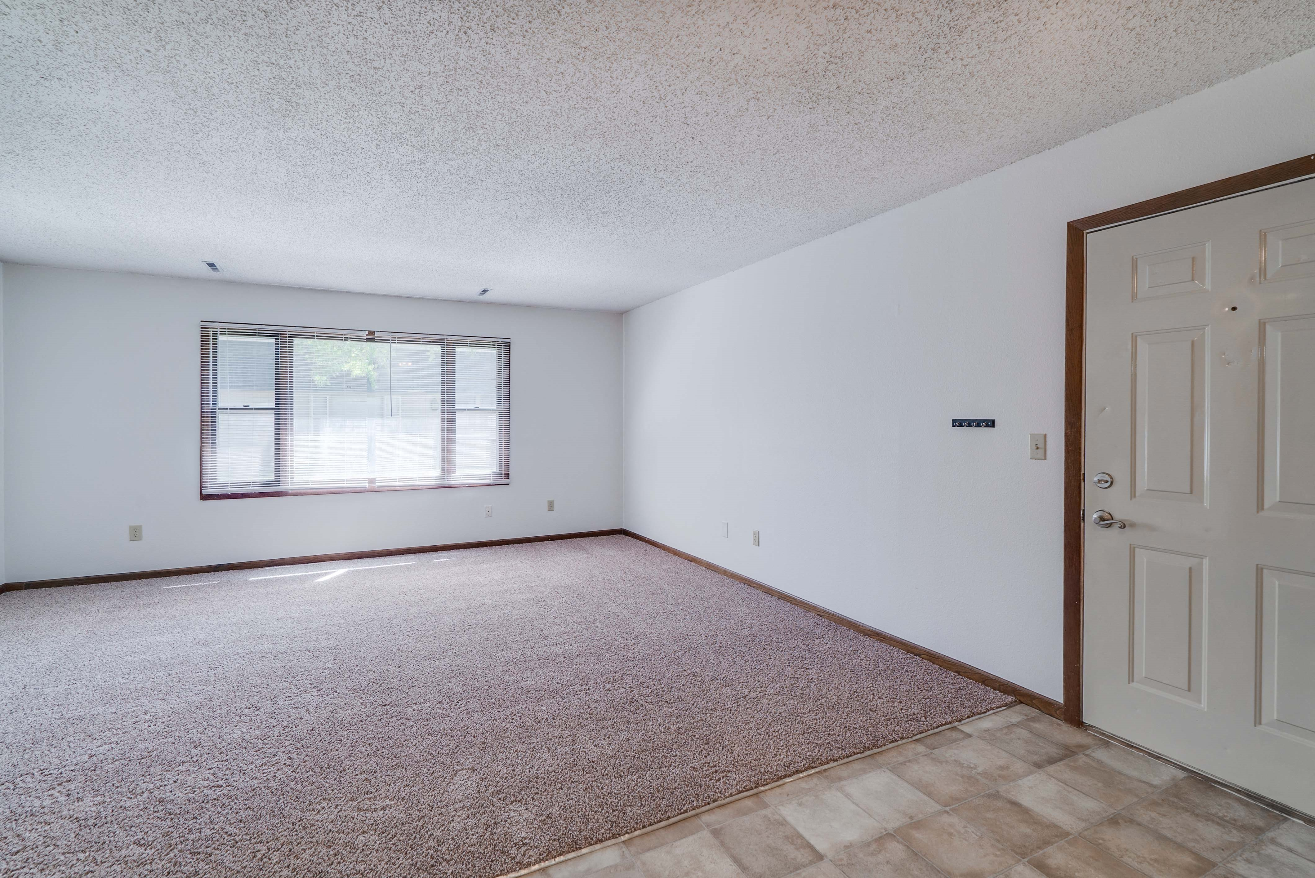 Open floor plan living space with large windows at South View Apartments