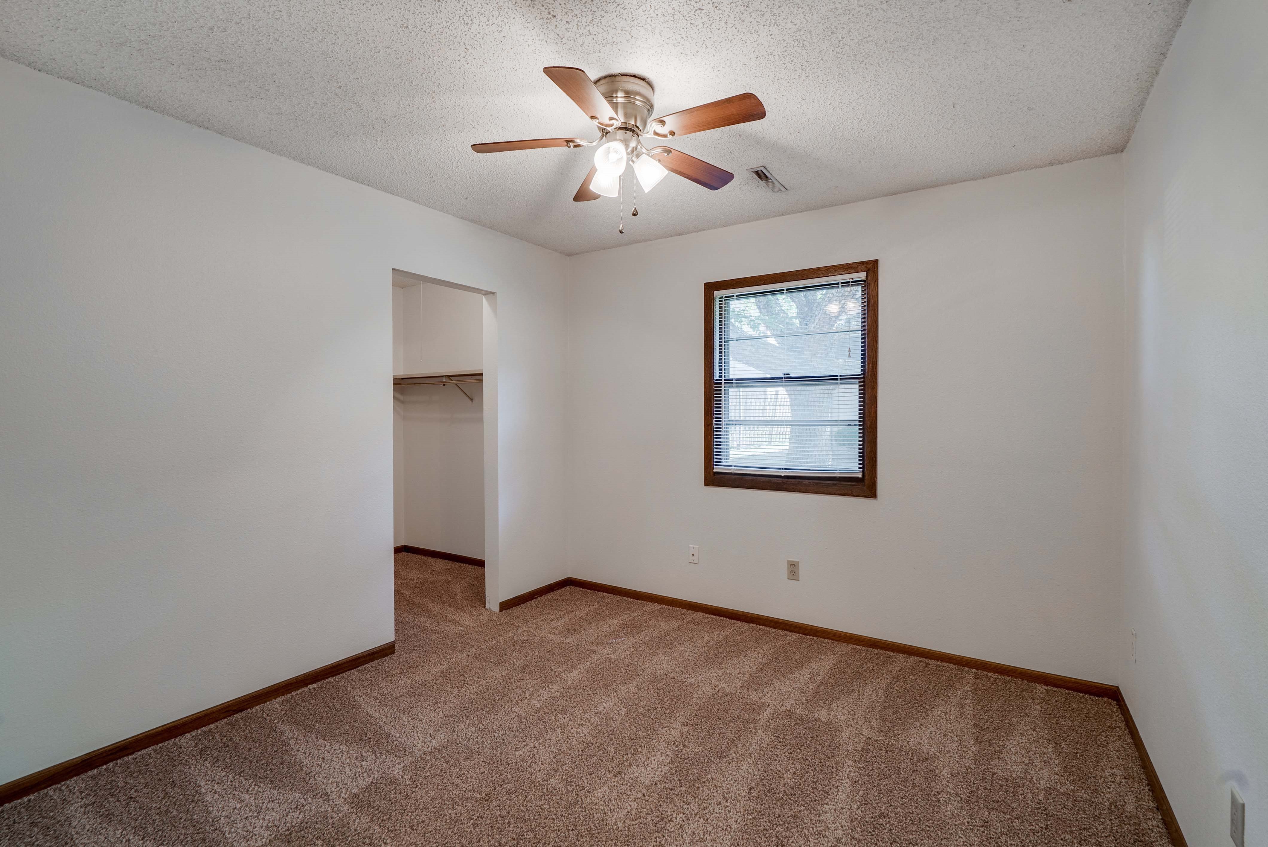 Bedroom with ceiling fan and walk in closet at South View Apartments