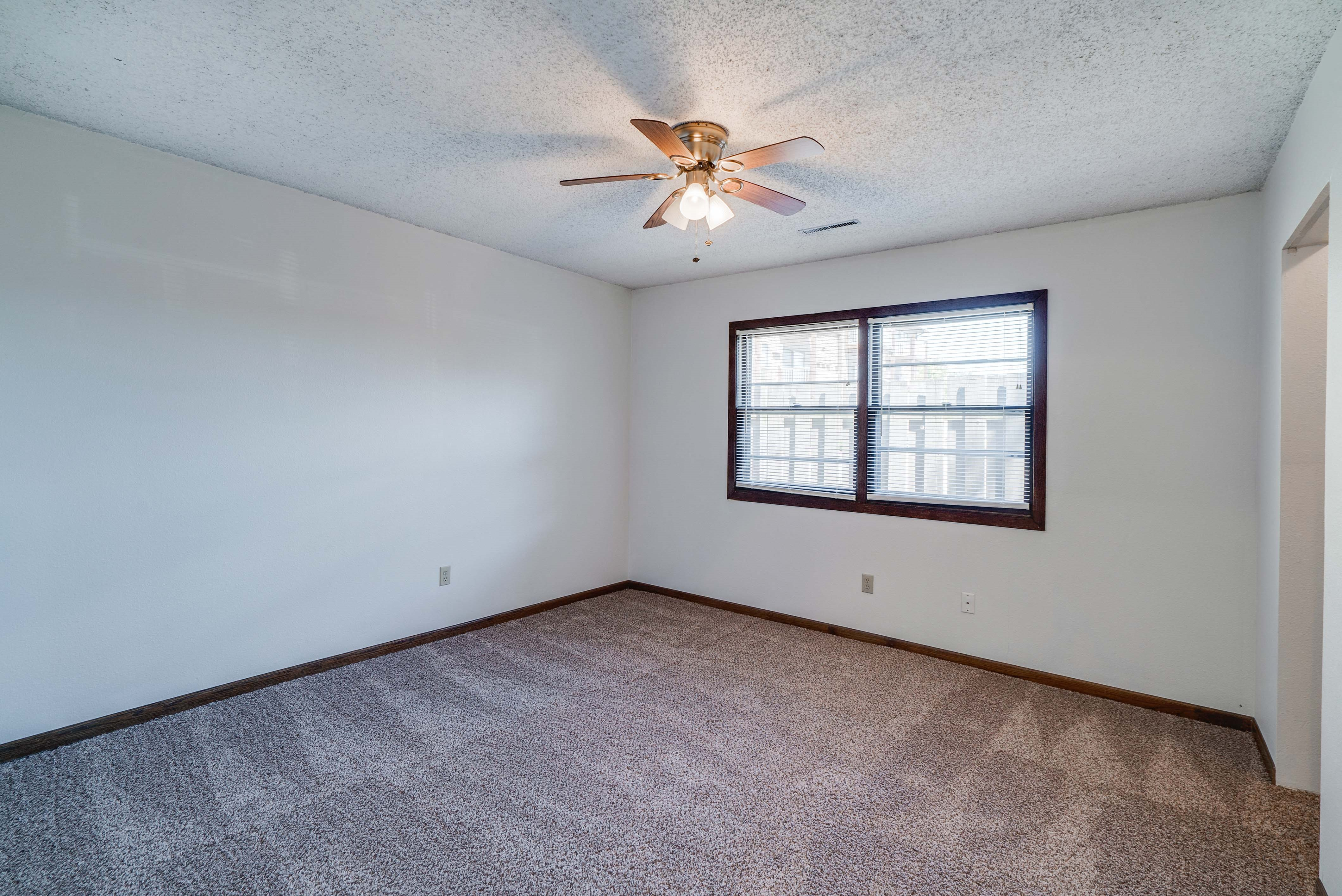 Bedroom with ceiling fan and large windows at South View Apartments