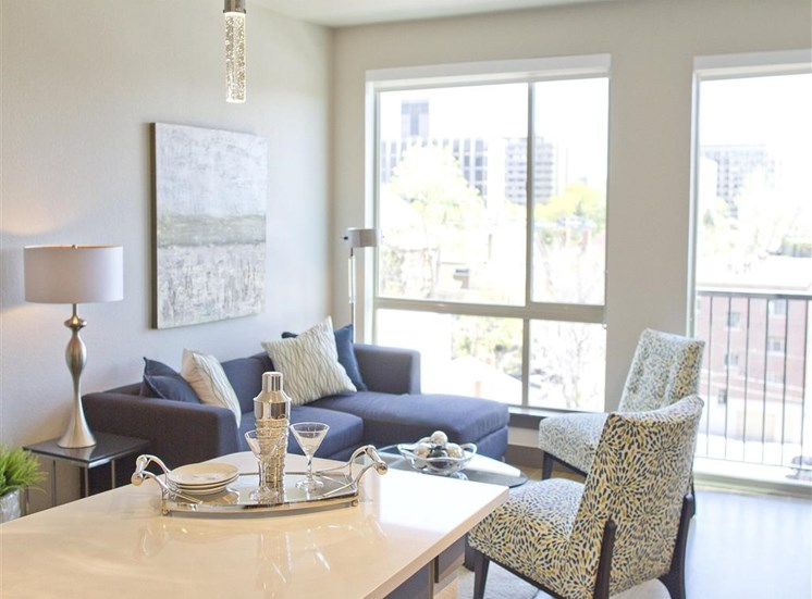 Over Sized Windows with Solar Shades in the background of furnished living room with kitchen bar