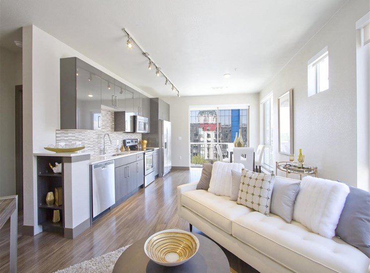 Living room model with couch next to kitchen with stainless appliances and track lighting