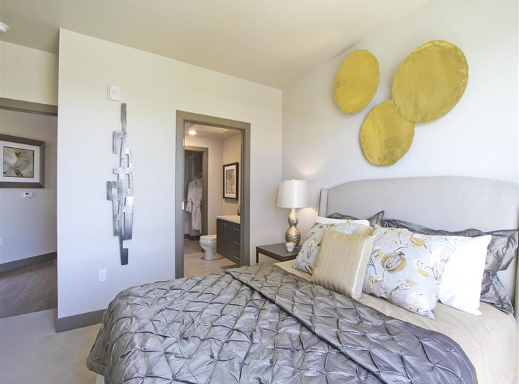 Bedroom model with large bed with white, gray bedding, night stand, lamp and wall decor